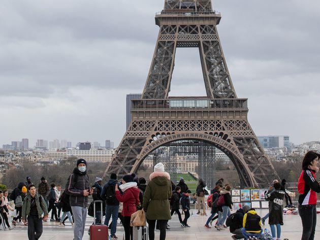 Des touristes devant la tour Eiffel à Paris le 12 mars