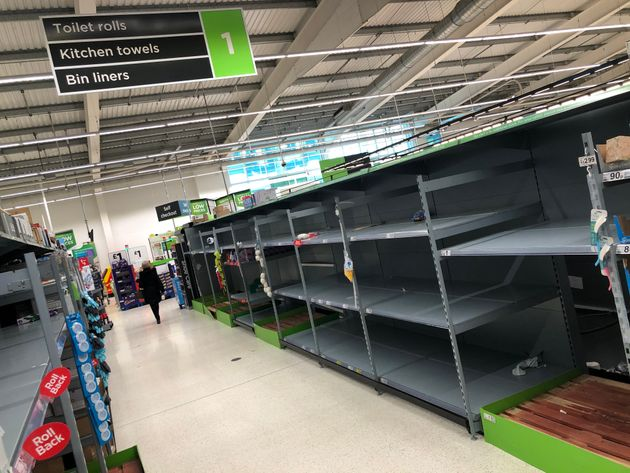 A view of empty shelves as toilet roll and kitchen roll are almost sold out in an Asda supermarket in...