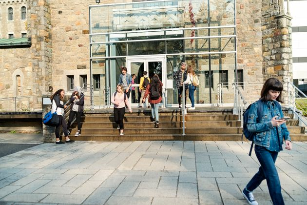 Students walk in and out of a university building in this stock photo. Colleges and universities in Canada's...