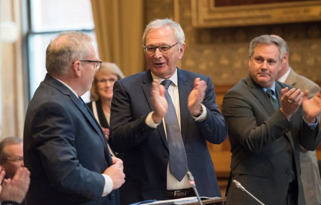 New Brunswick Finance Minister Ernie Steeves, left, is applauded by Premier Blaine Higgs and his colleagues...