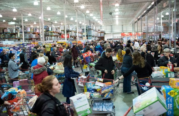 People line up at the cash registers at a Costco in Ottawa, amid growing concern about COVID-19, on Friday,...