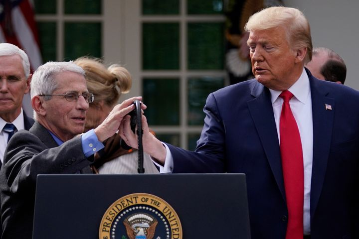 President Donald Trump adjusts the microphone for Dr. Anthony Fauci, director of the National Institute of Allergy and Infect