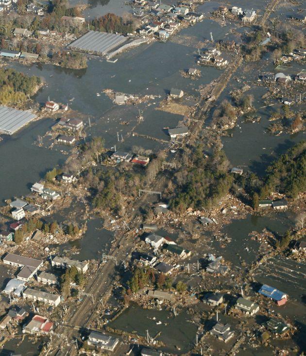 地震と津波により被害を受けた街。中央はJR常磐線の線路(宮城県上空)