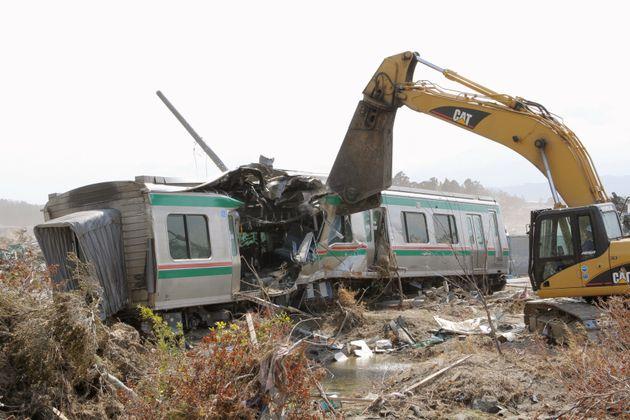 大津波を受けJR常磐線新地駅で脱線、転覆した列車の撤去作業が始まり、業者が重機を使って車体を解体した。スクラップにして運び出す予定という(福島・新地町)