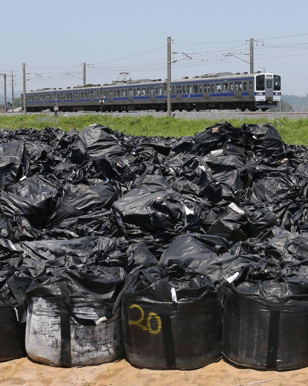 避難区域で初の鉄道運行を再開したJR常磐線・広野―竜田駅間を走行する列車。手前は集められた除染で出た汚染土など=6月1日午前、福島県楢葉町