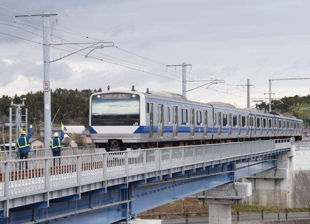 東日本大震災と東京電力福島第1原子力発電所事故により不通となっているJR常磐線で試運転が行われ、再建された橋を渡る列車=2019年12月18日、福島県双葉町