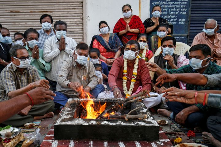 Hindu residents wearing protective masks perform prayers for protection against coronavirus disease (COVID-19), outside a temple, in Ahmedabad, Gujarat.