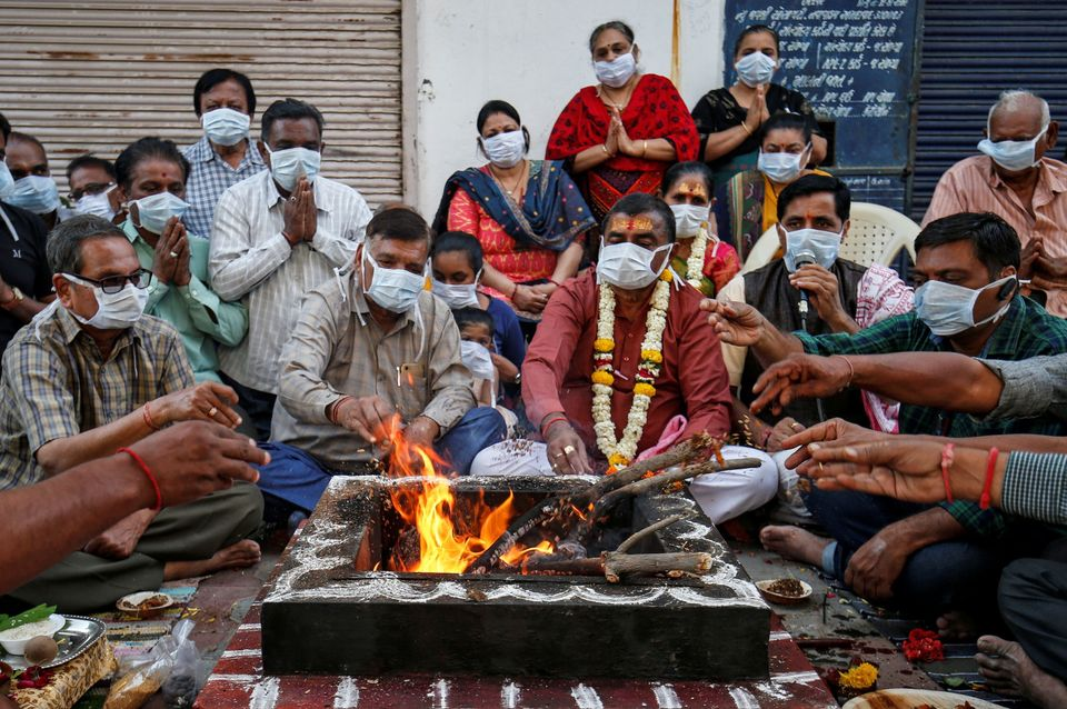 Hindu residents wearing protective masks perform prayers for protection against coronavirus disease (COVID-19),...