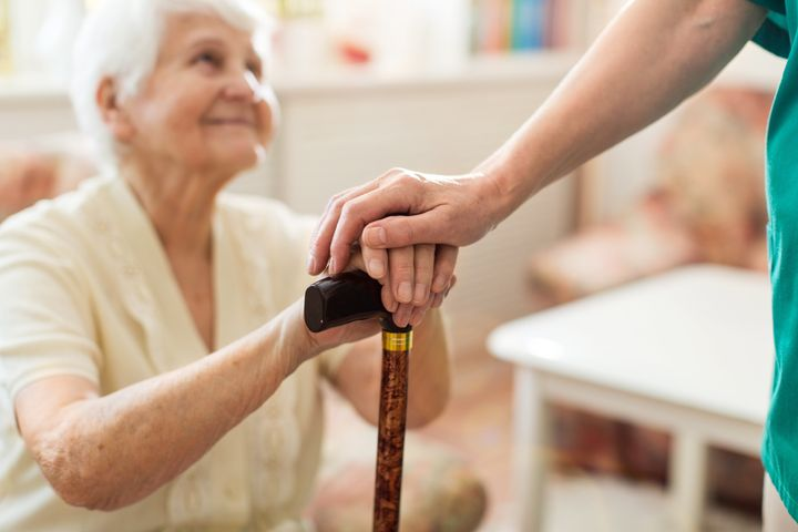 Close-up of woman holding senior's hands leaning on cane