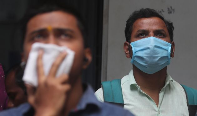 Indians cover their faces as they watch the stock exchange index at the BSE building in Mumbai on March...