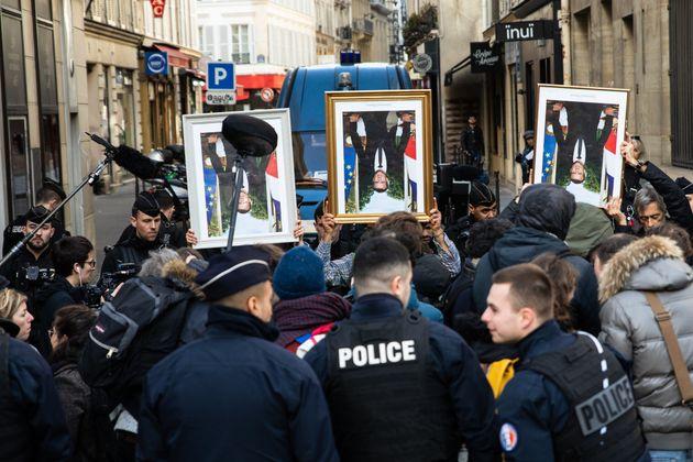 Une poignée de manifestants brandissant des portraits décrochés d'Emmanuel Macron...