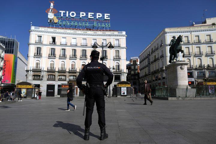 A police officer stands guard at Sol square in downtown Madrid, Spain, Saturday, March 14, 2020.
