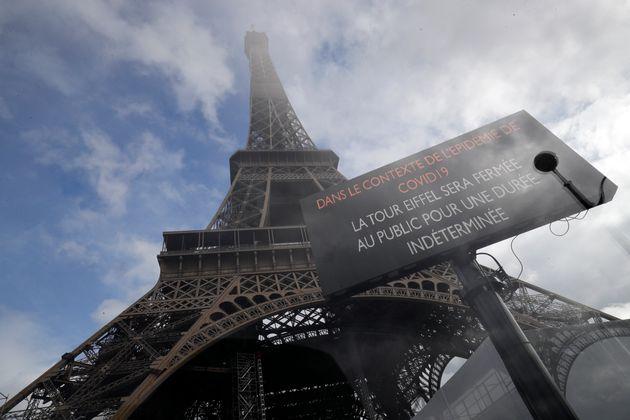 Une photo prise le 14 mars 2020 près de la tour Eiffel à Paris, montre une planche informant...