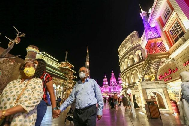People wear protective masks, following an outbreak of coronavirus, as they walk at Global Village in