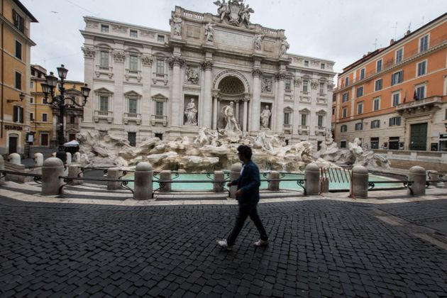 A man walks past the Trevi fountain in Rome, Saturday, March 14, 2020. Italians have been experiencing...