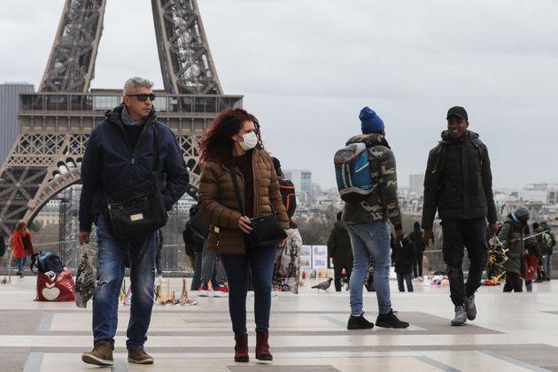 Des personnes devant la tour Eiffel à Paris, le 12 mars