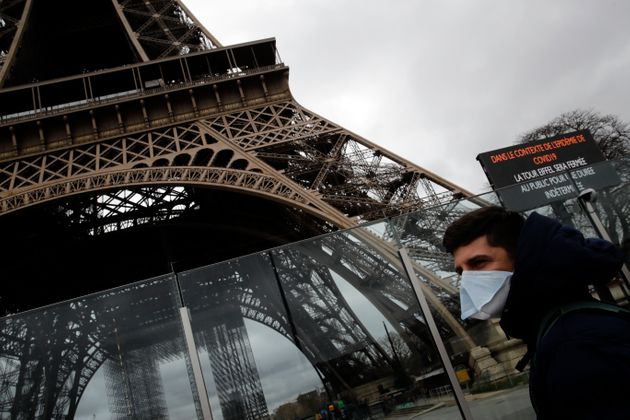 A man wearing a mask walks pasts the Eiffel tower closed after the French government banned all gatherings...