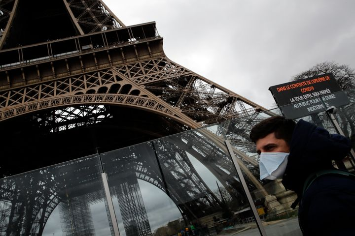 A man wearing a mask walks pasts the Eiffel tower closed after the French government banned all gatherings of over 100 people