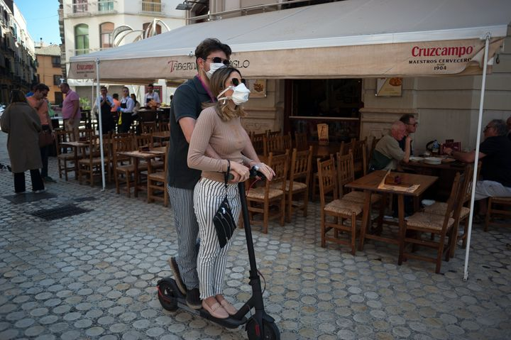 A couple wearing face masks as a precaution against the spread of coronavirus ride a scooter in downtown Malaga.
