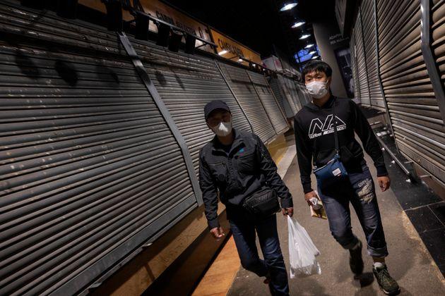 Tourists wearing masks walk past closed stalls at La Boqueria market in Barcelona, Spain, Saturday, March 14, 2020.