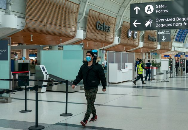 A man wears a mask as he walks through Terminal 3 at Pearson Airport in Toronto on Friday, March 13,