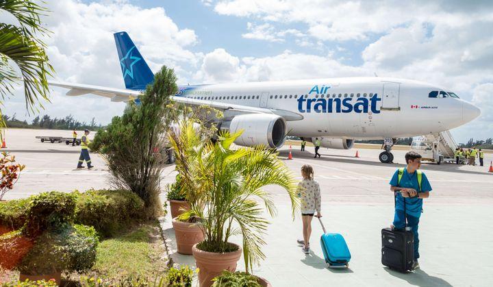 Passengers prepare to board an Air Transat airplane in Cuba on Feb. 19, 2016.