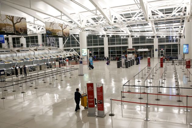 Few travelers are seen in a mostly empty flight check-in area at John F. Kennedy Airport's Terminal 1,...