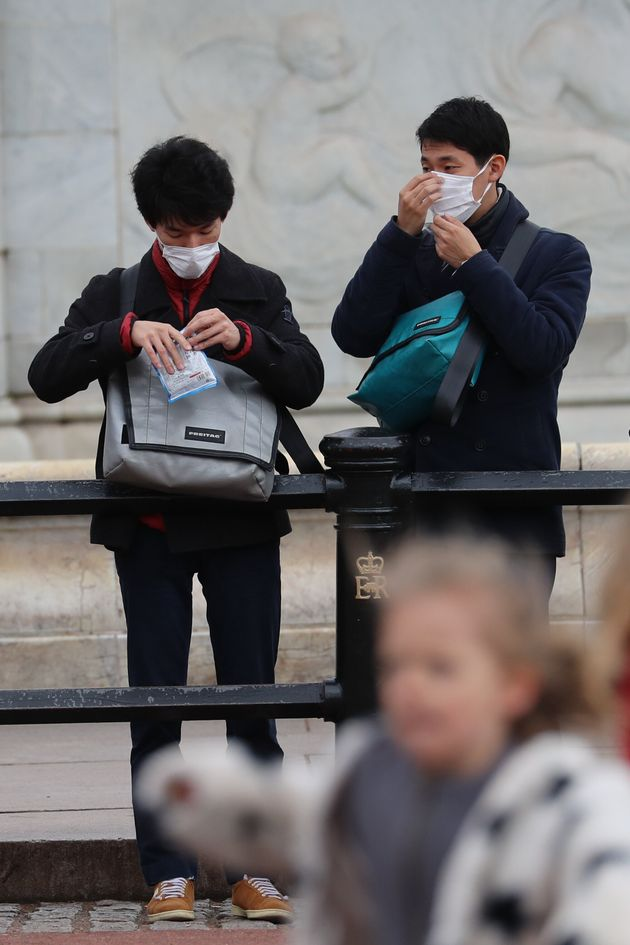 Tourists wearing face masks to protect against the spread of coronavirus outside of Buckingham Palace,...