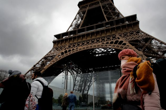 A woman wearing a mask walks pasts the Eiffel Tower closed after the French government banned all gatherings...