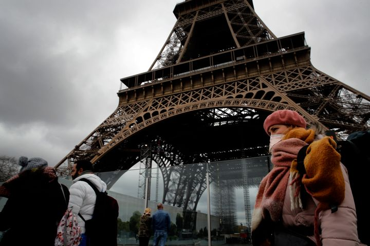 A woman wearing a mask walks pasts the Eiffel Tower closed after the French government banned all gatherings of over 100 peop