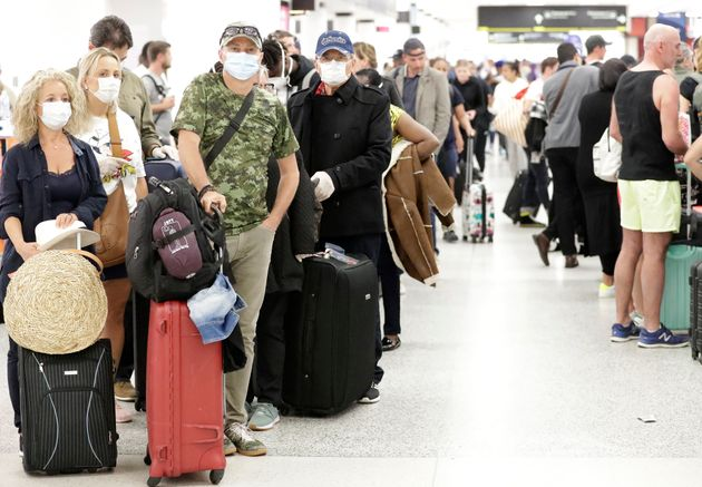 Travelers wearing surgical masks wait in line, Friday, March 13, 2020, at Miami International Airport...
