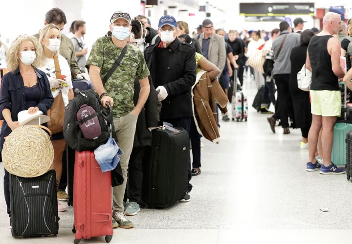 Travelers wearing surgical masks wait in line, Friday, March 13, 2020, at Miami International Airport in Miami. (AP Photo/Wil