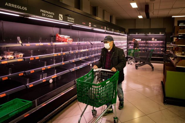 A man wearing a mask walks past empty shelves in a meat market in Barcelona, Spain, Saturday, March 14,...