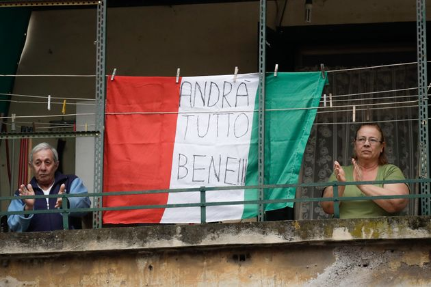 A couple applauds next to an Italian flag reading everything will be alright, at the Garbatella neighborhood,...