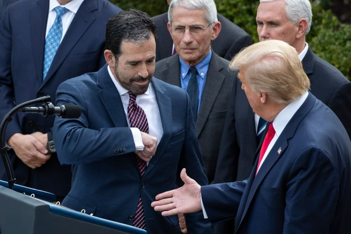 LHC Group's Bruce Greenstein elbow bumps with President Donald Trump during a news conference about the coronavirus on Friday