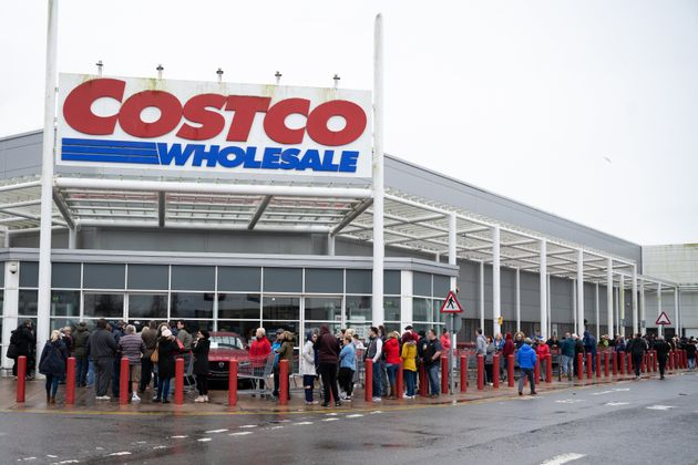 Customers queue to get into a Costco store which opens its doors at 11am in Cardiff.