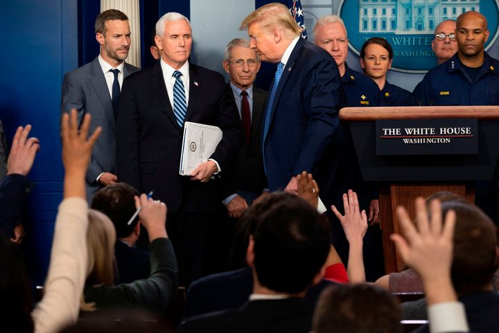 Reporters ask questions as President Donald Trump departs after speaking during a press briefing about the coronavirus on Sun