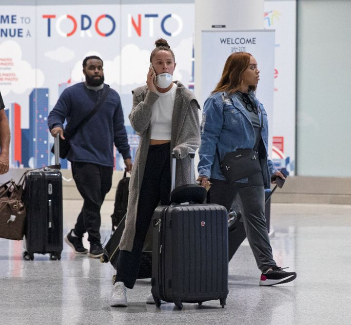 A traveller makes a phone call in the international arrivals lounge at Pearson Airport in Toronto, amid a growing global number of coronavirus March 13.