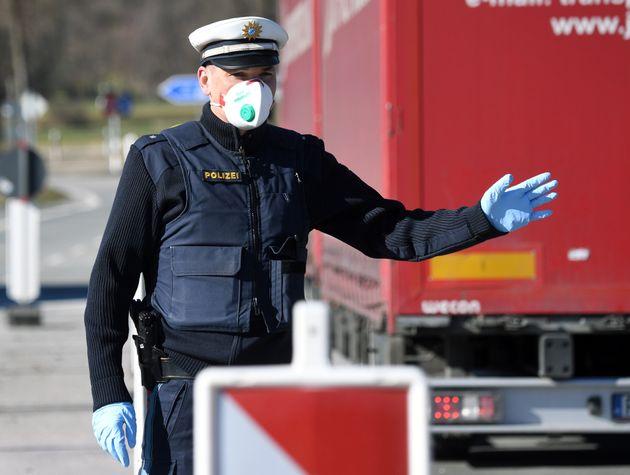 Un policier allemand portant un masque arrête un conducteur au poste frontière entre l'Autriche...