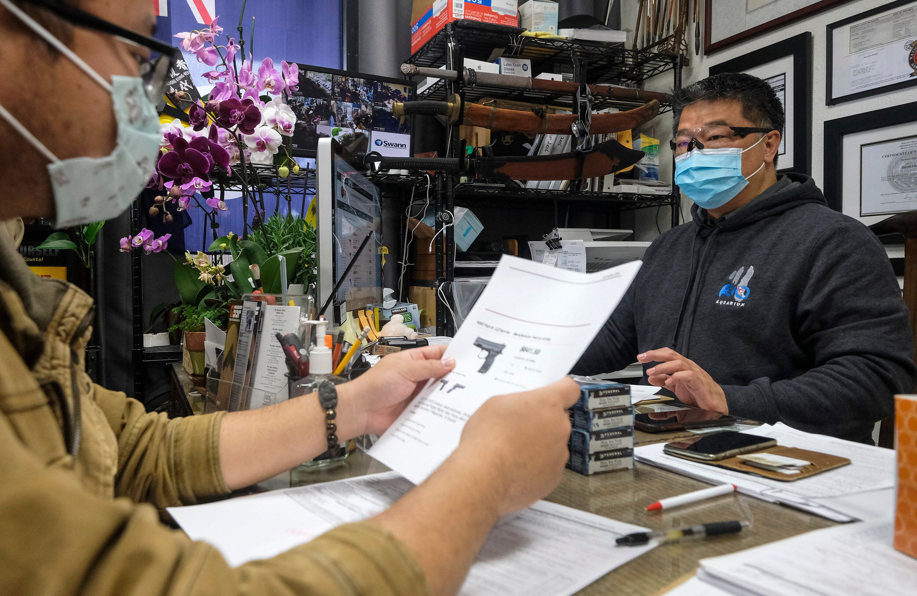 David Liu, right, owner of a gun store, takes an order from a customer in Arcadia, Calif., Sunday, March 15, 2020.
