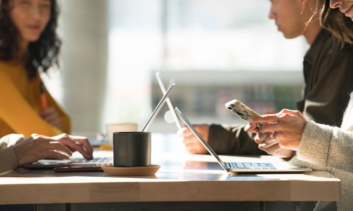 This stock photo shows young people working on laptops at a cafe.Canadian telecoms are making it more affordable for customers to stay in touch.