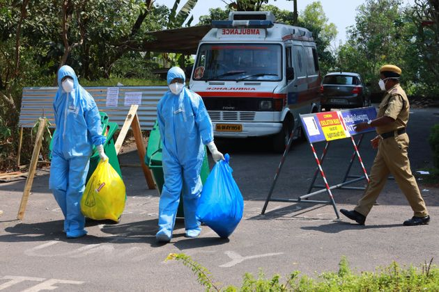 Heath officials in full protective gear carry medical waste out of an isolation ward of Ernakulam medical...