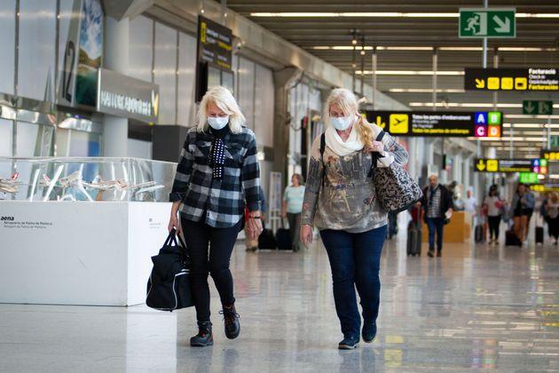 Deux touristes portant un masque face au coronavirus à l'aéroport de Palma de Majorque...