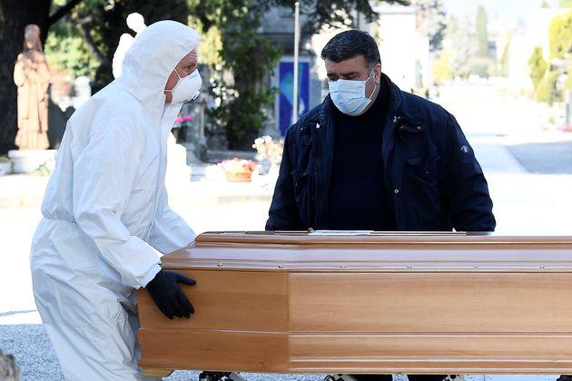 Dos operarios mueven el ferétro de una persona fallecida con coronavirus, en el cementerio de...