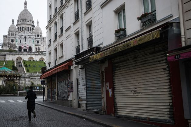 A man runs near the Sacre Coeur Basilica in the Montmartre area in Paris on March 16, 2020, as all non-essential...