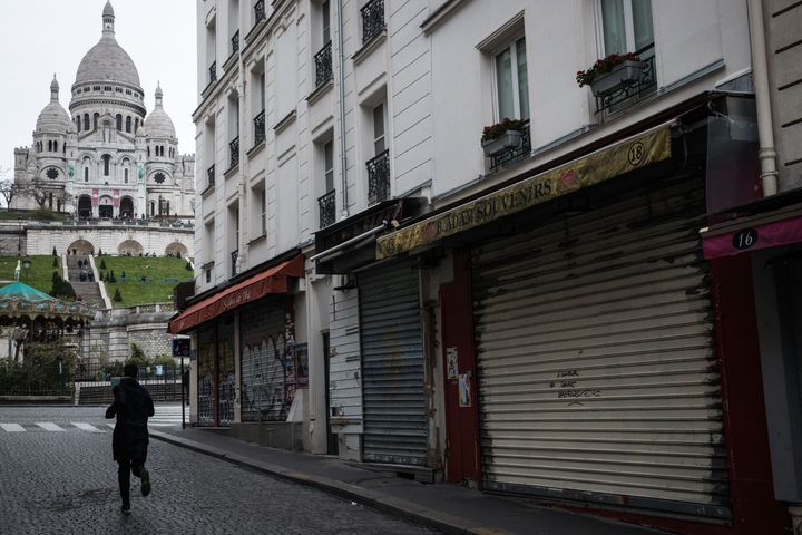 A man runs near the Sacre Coeur Basilica in the Montmartre area in Paris on March 16, 2020, as all non-essential public places including restaurants and cafes have been closed to contain the spread of the COVID-19, caused by the novel coronavirus.