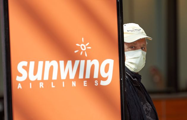 Un homme portant un masque attend son bord à côté d'un panneau canadien Sunwing à l'aéroport international...