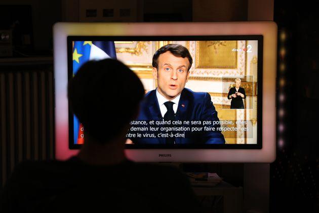 한 시민이 에마뉘엘 마크롱의 대국민 기자회견을 시청하고 있다. 파리, 프랑스. 2020년