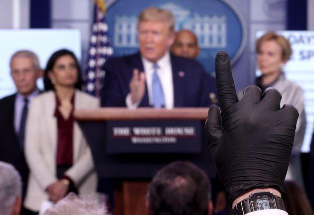 도널드 트럼프 미국 대통령 등이 참석한 코로나19 브리핑에서 한 언론인이 고무장갑을 착용한 채 손을 들어 질문을 신청하고 있다. 2020년