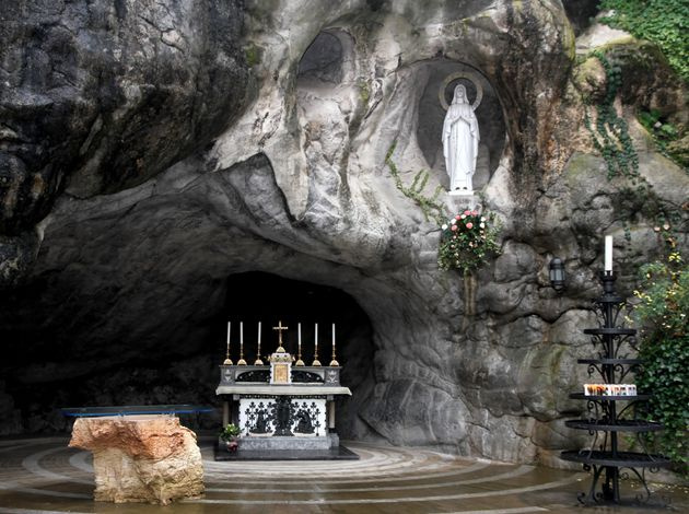 Statue of the Virgin Mary in the grotto of Lourdes attracts many pilgrims from all over the world